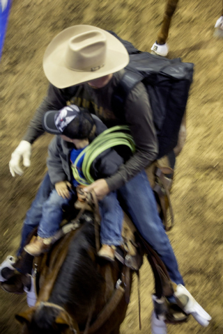 National Finals Rodeo team roper contestant Justin Davis and his son, Ryder, 3, ride at the Thomas & Mack Center on Tuesday. (Jeff Scheid/Las Vegas Review-Journal)
