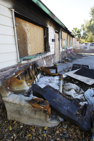 Burned furniture sits in front of the fire ravaged home at 2017 Balzar Ave. in North Las Vegas on Nov. 30, 2013. (Jason Bean /Las Vegas Review-Journal)