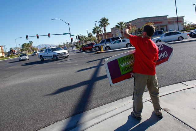 Sign-spinner Matthew Barnabi waves to passing card as he holds a sign advertising a nearby Pardee Homes development, at the intersection of Ann Road and Camino Eldorado in North Las Vegas on Satur ...