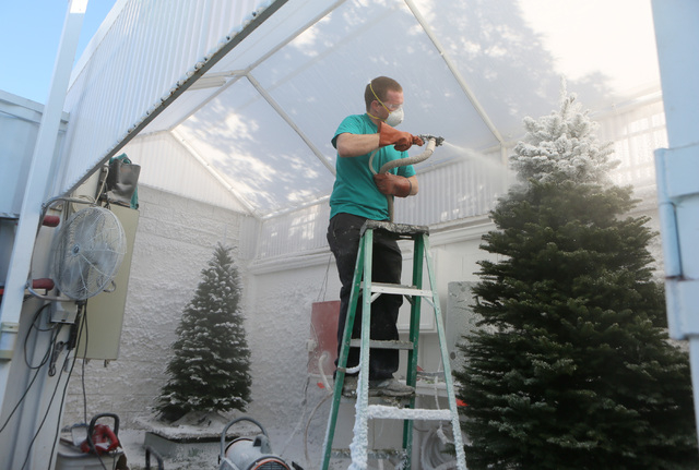 David Carter applies custom flocking to create a snow-like effect on a Noble Fir tree at Deerbrooke Farm tree lot on Thursday. Deerbrooke Farm is family-owned and operated by Clark County firefigh ...