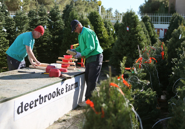 Scott Muller, left, and Steve Phillips construct tree stands at Deerbrooke Farm tree lot on Thursday.  Deerbrooke Farm is family-owned and operated by Clark County firefighter Steve Phillips. (Ron ...