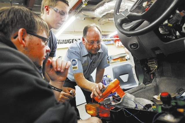 Boulder City High School teacher Rodney Ball, right, works with students Preston Black, left, and Jared Mooney on auto repair in the school in Boulder City, Nev. Tuesday, Dec. 17, 2013. (John Loch ...