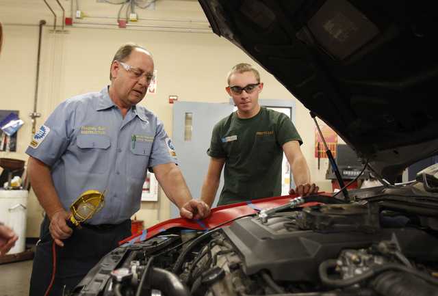 Boulder City High School teacher Rodney Ball, left, works with student William Lassley on auto repair in the school in Boulder City, Nev. Tuesday, Dec. 17, 2013. (John Locher/Las Vegas Review-Journal)
