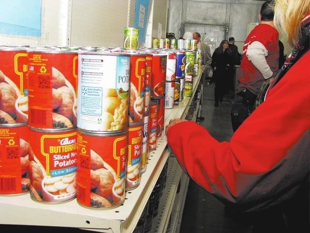 Bank of America volunteers help stock shelves Dec. 11 at Lutheran Social Services of Nevada, 73 Spectrum Blvd., after presenting a check for $14,800. The nonprofit plans to convert one of its offi ...