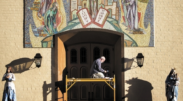 Greg Barnaby paints at Saint Joan of Arc Catholic Church, 315 S. Casino Center Boulevard, on Thursday, Dec 12, 2013. Barnaby has spent the last five weeks repainting the statutes and exterior at t ...