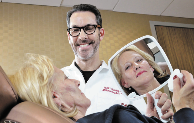 Debbie Hale poses with Dr. Terry Higgins after having injections of Botox and compounds used to fill hollows in the face and make cheekbones look fuller at Anson and Higgins Plastic Surgery Associ ...