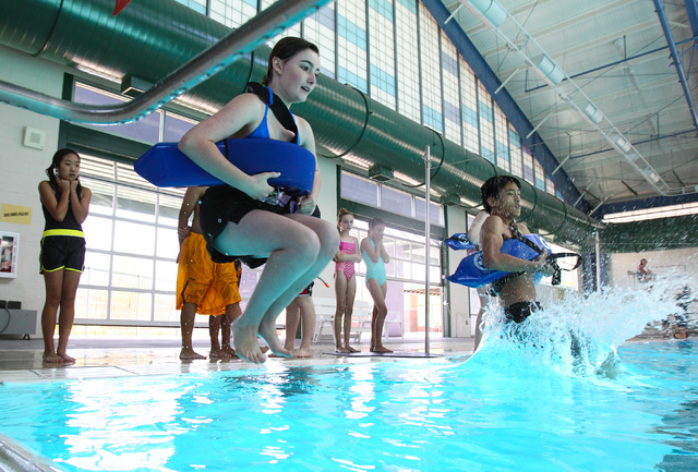 Thirteen-year-old Zoe Kaplan, left, and Simon Lin, 14, take their turn jumping properly into the pool during the Junior Lifeguard Camp at the Pavilion Center Pool in Las Vegas on Monday, June 17,  ...