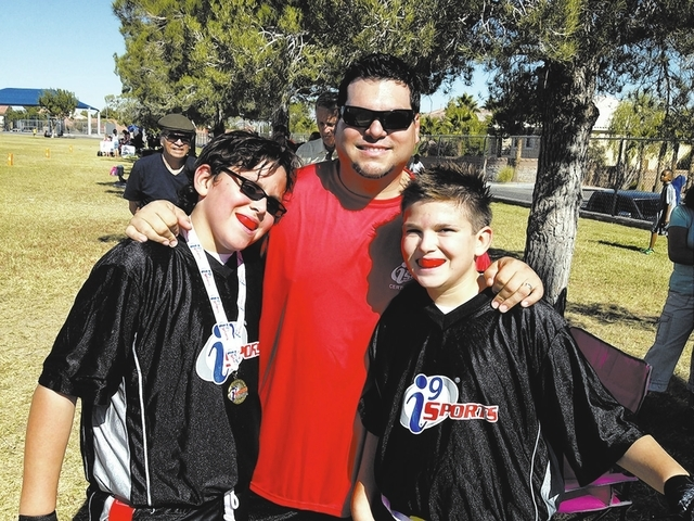 From left, Cross Castillo, 9, his father, Michael, and brother Timothy, 12, take a break at an i9 Sports event at a Spring Valley school in the fall. i9 Sports promotes flag football over contact  ...