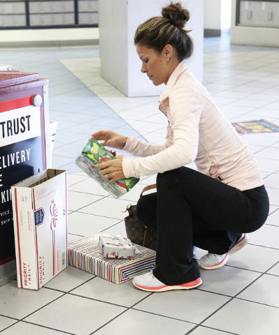 Jamie Little, of Las Vegas, places Christmas presents in boxes for mailing at the Summerlin branch of the U.S. Post Office in Las Vegas Wednesday. (Jerry Henkel/Las Vegas Review-Journal)