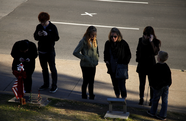 People read a plaque in Dealey Plaza in Dallas Tuesday, Dec. 31, 2013. Behind them a white X marks a spot where President John F. Kennedy was shot. (John Locher/Las Vegas Review-Journal)