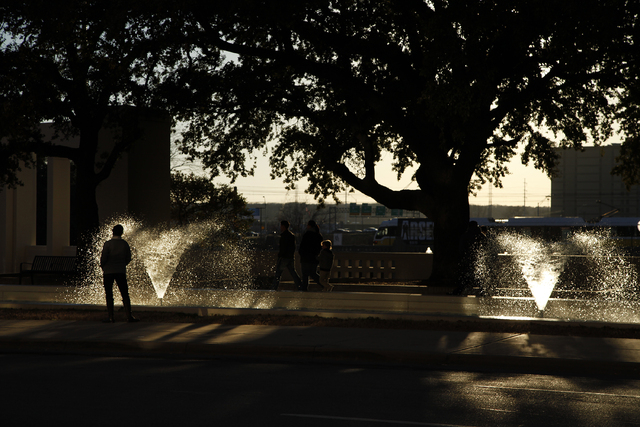 A woman walks by a fountain in Dealey Plaza in Dallas Tuesday, Dec. 31, 2013. (John Locher/Las Vegas Review-Journal)