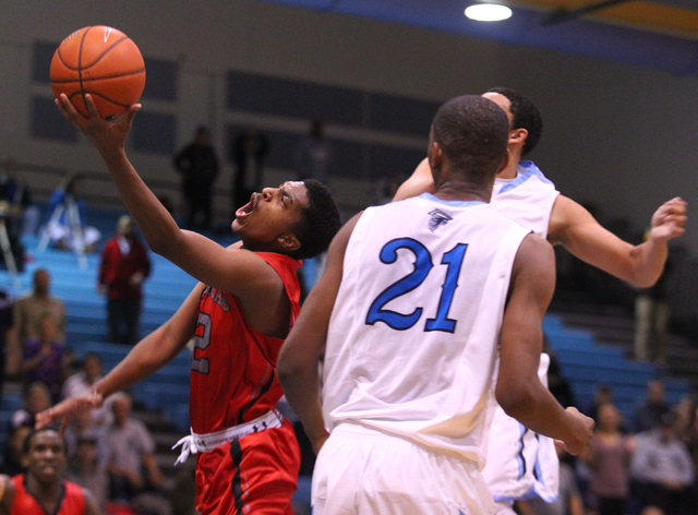 Las Vegas' Devon Colley (12) lays up over Foothill's Torrance Littles (21) during a game at Foothill High School in Henderson on Tuesday, Dec. 10, 2013. (Chase Stevens/Las Vegas Review-Journal)