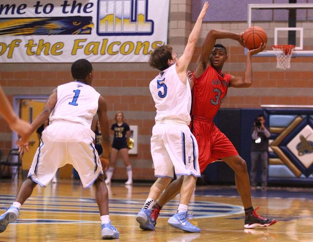 Las Vegas' Re'Kwon Smith (34) looks to pass as Foothill's Matt Rapp (5) reaches in during a game at Foothill High School in Henderson on Tuesday, Dec. 10, 2013. (Chase Stevens/Las Vegas Review-Jou ...