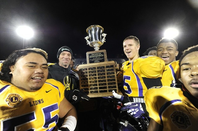 Team Sunrise head coach Brian Castro, left center, of Green Valley High School and tight end Austin Hunt, of Silverado High School hoist the trophy after defeating Team Sunset 27-23 during the 42n ...