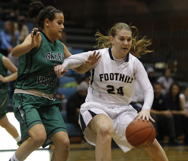 Foothill High School player Gabby Doxtator, right, drives by Milena Palor of Green Valley during their game at Foothill High School in Henderson, Nev. Tuesday, Dec. 17, 2013. (John Locher/Las Vega ...