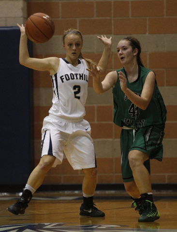 Green Valley High School player Brooke Haney, right, passes by Mikayla Yeakel of Foothill High School during their game at Foothill High School in Henderson, Nev. Tuesday, Dec. 17, 2013. (John Loc ...