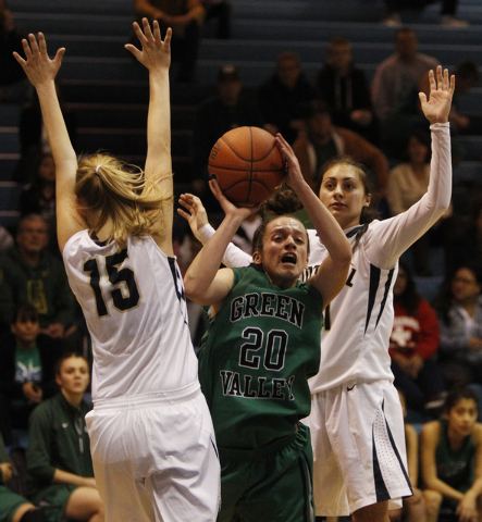 Green Valley High School player Rianna Rudolph, center, tries to drive through Nicole Benson, left, and Taylor Turney of Foothill High School during their game at Foothill High School in Henderson ...