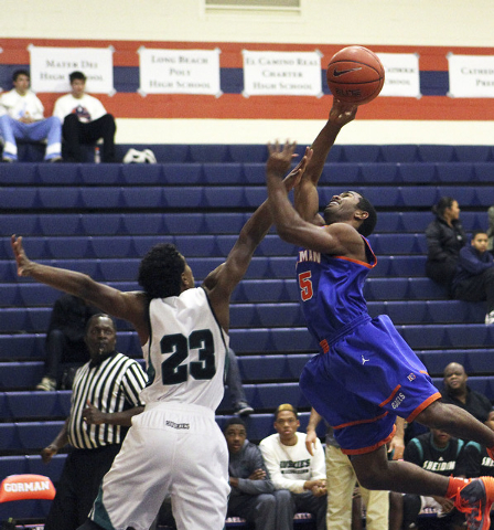 Gorman's Miles Loupe (5) goes up for a shot while Sheldon's Devin Greene (23) defends during their game in the Tarkanian Classic at Bishop Gorman High School in Las Vegas, Thursday, Dec. 19, 2013. ...