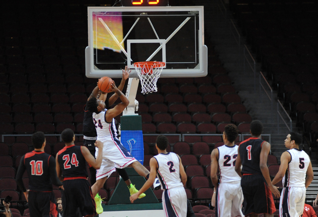 Findlay Prep basketball player Craig Victor, number 24 in white, goes in for a layup against the Prime Prep Academy defense during the Tarkanian Classic held at the Orleans Arena in Las Vegas Frid ...