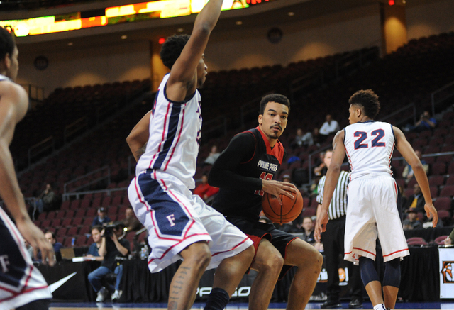 Prime Prep Academy basketball player Micah Seaborn, center, makes a move against the Findlay Prep defense during the Tarkanian Classic held at the Orleans Arena in Las Vegas Friday, Dec. 20, 2013. ...