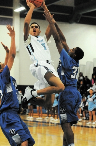 Canyon Springs Jordan Davis (3) takes a shot against Desert Pines Jordan Simon (32), right, and Coby Myles (15) at home, Thursday, Dec. 5, 2013. Canyon Springs won the game 66-61 against the Jagua ...