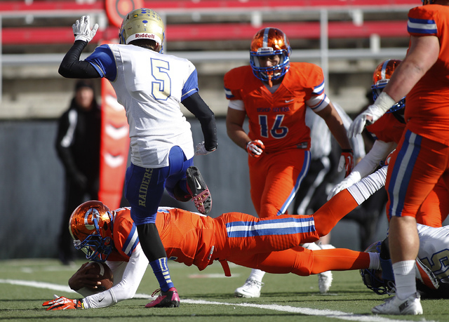 Bishop Gorman quarterback Randall Cunningham Jr. (12) dives into the end zone for a touchdown in front of Reed High School's Allen Mahlin (5) during the Division I Nevada State Football championsh ...