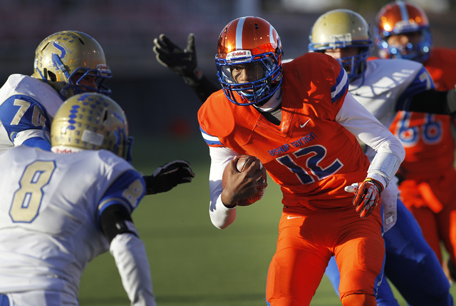 Bishop Gorman quarterback Randall Cunningham Jr. (12) looks for running room past Reed High School's Austin Warner (8) and Calvin Cox (70)  during the Division I Nevada State Football championship ...