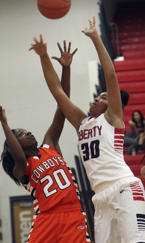 Liberty's Paris Strawther (30) goes high for the ball over Chaparral's Marcia Hawkins (20) during their game at Liberty High School in Henderson, Monday, Dec. 2, 2013.  (Jerry Henkel/Las Vegas Rev ...