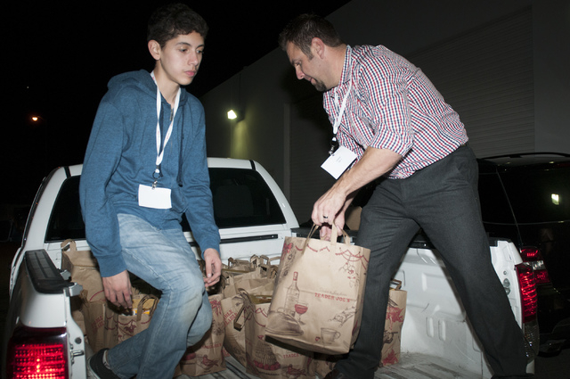 Volunteers Elijah Mayorga, left, and Clay Bloxham, organize bags of food on a truck to be delivered to a local high school during an event at Project 150 in Las Vegas where volunteers were planned ...