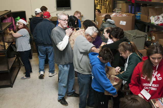 Volunteers organize bags of food during an event at Project 150 in Las Vegas where volunteers were planned to assemble more than 750 holiday dinners for local students and their families in need,  ...