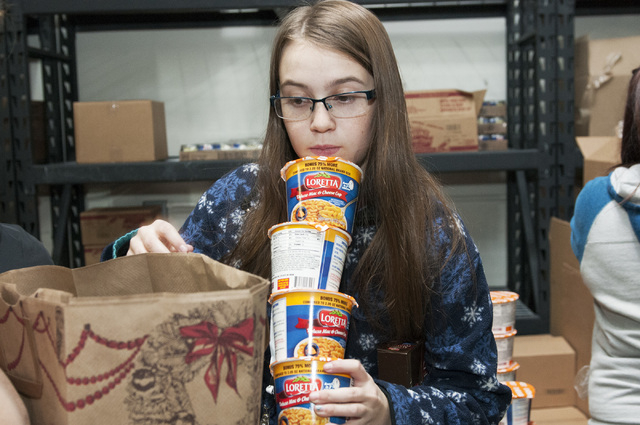 Volunteer Ka'lina Pugmire, 13, organizes cups of mac and cheese inside a bag during an event at Project 150 in Las Vegas where volunteers were planned to assemble more than 750 holiday dinners for ...