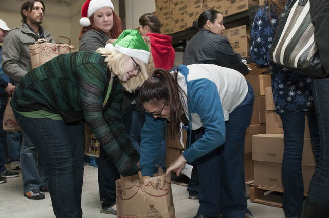 Volunteers Sara Thomson, left and Alexis Figueroa, organize a bag of food during an event at Project 150 in Las Vegas where volunteers were planned to assemble more than 750 holiday dinners for lo ...