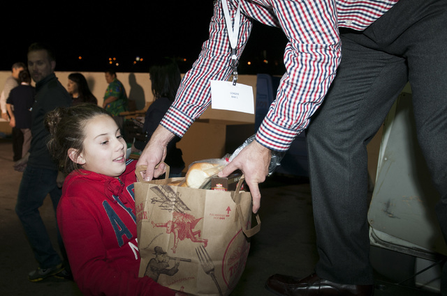 Volunteer Clay Bloxham, right, helps her daughter Grace, 11, to load a bag of food inside a truck during an event at Project 150 in Las Vegas where volunteers were planned to assemble more than 75 ...