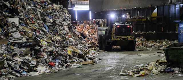 A bulldozer begins the sorting process of recently unloaded recyclables at the Republic Services sorting facility at 333 West Gowan Road in North Las Vegas Friday, Dec. 21, 2013. Republic Services ...