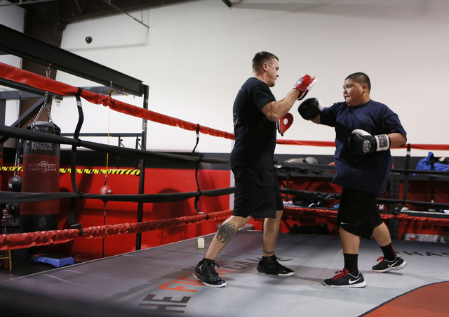 Steve Call, left, founder of Relentless Youth Boxing Club, spars with Alijah Shumpert (cq), 14, during a workout at Phase 1 Sports gymnasium and training facility Saturday, Dec. 21, 2013, in Las V ...