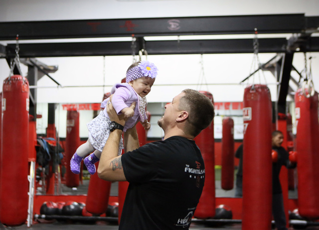 Steve Call, center, founder of Relentless Youth Boxing Club, visits momentarily with the daughter Yazmin Valencia of his student Jason Valencia, back right, during a workout at Phase 1 Sports gymn ...