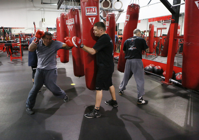 Jason Valencia, left, spars with Steve Call, center, founder of Relentless Youth Boxing Club during a workout at Phase 1 Sports gymnasium and training facility Saturday, Dec. 21, 2013, in Las Vega ...