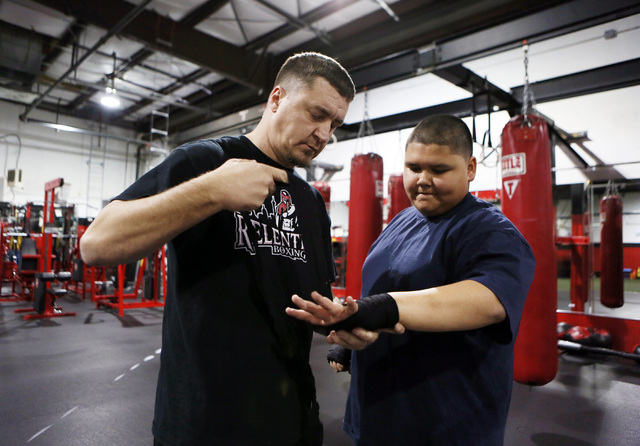 Steve Call, left, founder of Relentless Youth Boxing Club, helps Alijah Shumpert (cq), 14, wrap his hands during a workout at Phase 1 Sports gymnasium and training facility Saturday, Dec. 21, 2013 ...