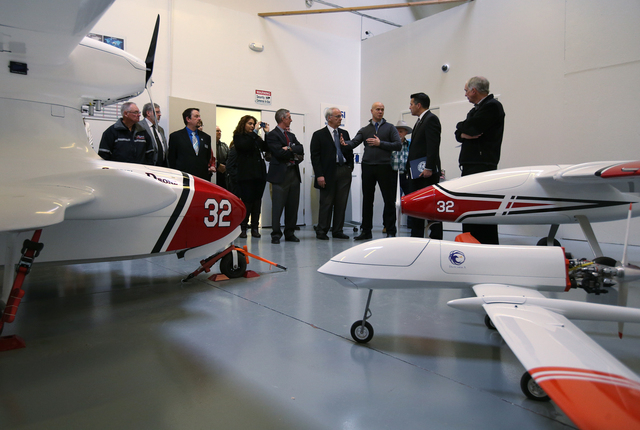 Surrounded by protypes, Drone America founder Mike Richards, center, talks with Nevada Gov. Brian Sandoval and local business representatives during a Cabinet Business Visit Day stop, in Reno, Nev ...