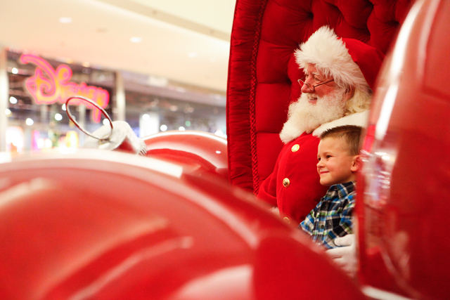Five-year-old Kason Duke of Las Vegas poses for a photo with a man dressed as Santa Claus, who declined to give his name, outside of Macy's at the Fashion Show Mall in Las Vegas on Dec. 7, 2013. ( ...