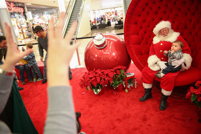 Ann Frehner, motions to her son, 11-month-old son Grayson, as he sits for a photo with a man dressed as Santa Claus, who declined to give his name, outside of Macy's at the Fashion Show Mall in La ...