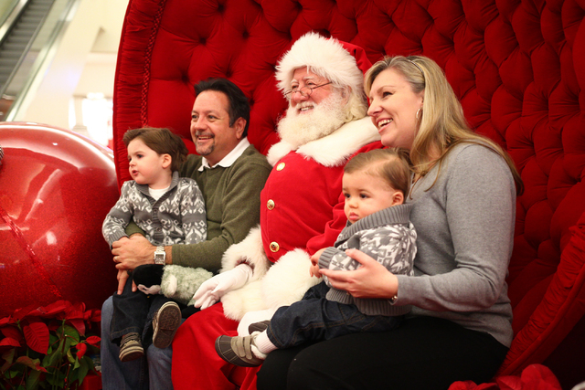 Ann Frehner, holds 11-month-old son Grayson, with husband Michael on left, holding 2-year-old Spencer, while posing for a photo with a man dressed as Santa Claus, who declined to give his name, ou ...