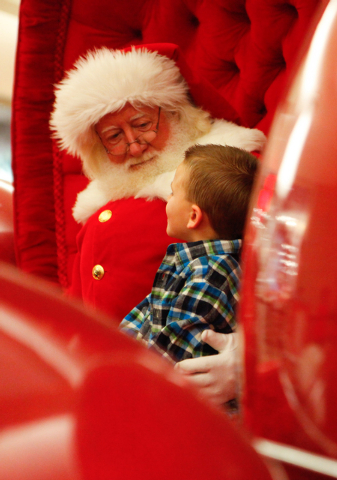 Five-year-old Kason Duke of Las Vegas talks before taking a photo with a man dressed as Santa Claus, who declined to give his name, outside of Macy's at the Fashion Show Mall in Las Vegas on Dec.  ...