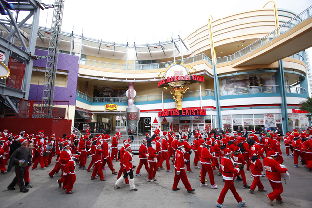 People walk through the Fremont Street Experience to the start line for the Great Santa Run in downtown Las Vegas on Saturday, Dec. 7, 2013. Over 11,000 people participated in the 5k run and 1 mil ...