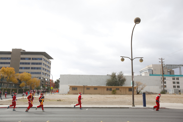 People run on Carson Avenue during the Great Santa Run in downtown Las Vegas on Saturday, Dec. 7, 2013. Over 11,000 people participated in the 5k run and 1 mile walk. (Chase Stevens/Las Vegas Revi ...
