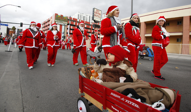 Three-year-old Niko Reynoso is pulled along down Fremont Street in the Great Santa Run in downtown Las Vegas on Saturday, Dec. 7, 2013. Over 11,000 people participated in the 5k run and 1 mile wal ...