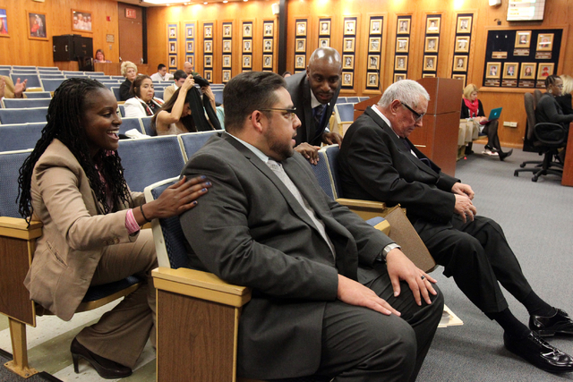 Stavan Corbett, center, is congratulated by fellow candidates Tara Raines, left, and Charles M. Ware after he is named Clark County School Board District D trustee during a special board meeting a ...