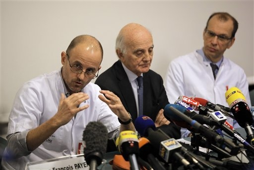 Professor Jean-Francois Payen, left, answers a journalist's question,  as Professor Gerard Saillant, center, and Professor Emmanuel Gay, right, look on, during a press conference at the Grenoble h ...