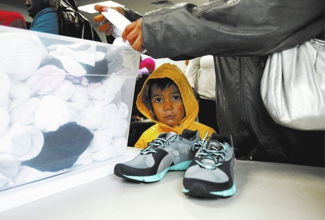 Joshua Ramierez, 3, waits while his mom Fabiola Aguilar receives free shoes and socks at the Salvation Army Friday, Nov. 22, 2013.  (John Locher/Las Vegas Review-Journal)