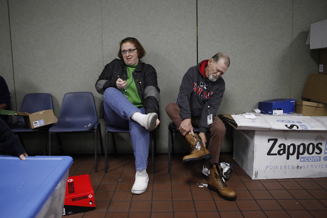 Melissa Arbour, left, and Ben Millership try on shoes at the Salvation Army Friday, Nov. 22, 2013.  (John Locher/Las Vegas Review-Journal)